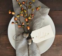 White plate with linen napkin and seasonal dried berries tied with note that says Thankful