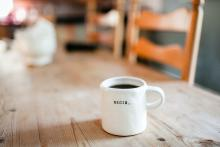 January 2021 photo writing prompt (word BEGIN on a white coffee mug sitting on a wooden kitchen table)