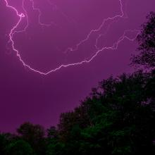 April '21 photo writing prompt_image of lightning against dark purplish sky over darkened trees